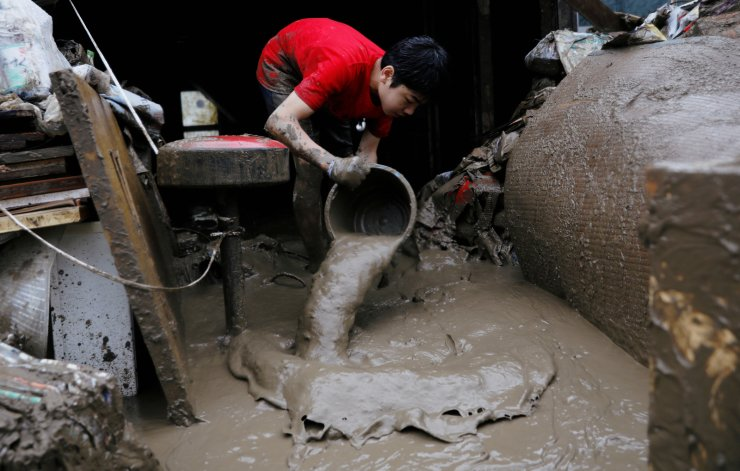 A boy cleans out mud from his house after floods caused by torrential rain swept through Hitoyoshi, Kumamoto Prefecture, southwestern Japan, July 9, 2020. REUTERS