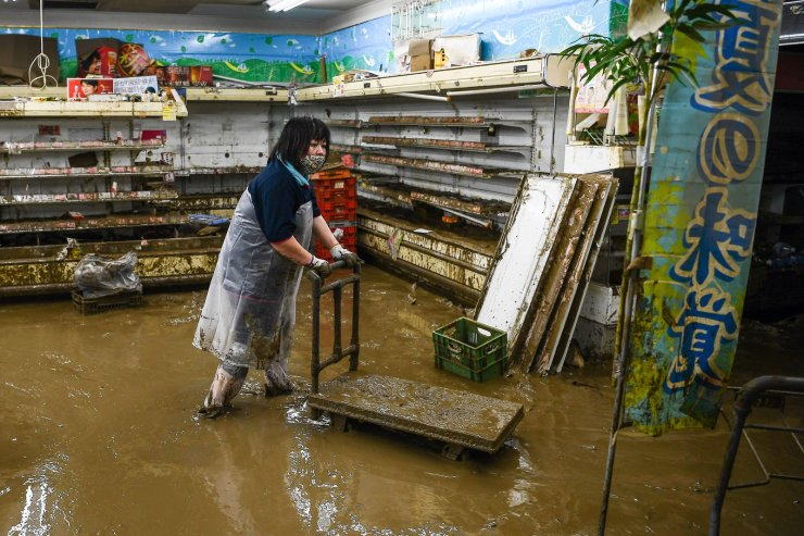 A woman wades in mud waters in a supermarket following heavy rains and flooding in Hitoyoshi, Kumamoto prefecture on July 9, 2020. - Japan will deploy more troops to search for survivors of devastating floods and landslides that have killed at least 52 people in the southwest of the country, Prime Minister Shinzo Abe pledged. AFP