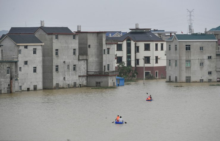 This photo taken on July 15, 2020 shows residents riding boats at a flooded area near the Poyang Lake due to torrential rains in Poyang county, Shangrao city in China's central Jiangxi province. AFP
