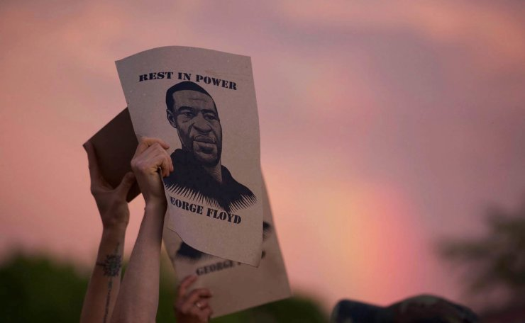 A protester holds a sign with an image of George Floyd during protests Wednesday, May 27, 2020, in Minneapolis against the death of Floyd in Minneapolis police custody earlier in the week. AP
