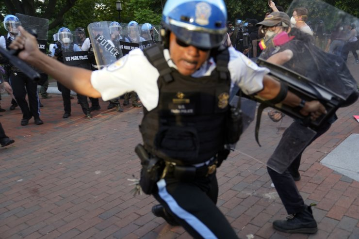 An officer swings a baton as demonstrators clash with police as they protest the death of George Floyd, Saturday, May 30, 2020, near the White House in Washington. Floyd died after being restrained by Minneapolis police officers. AP