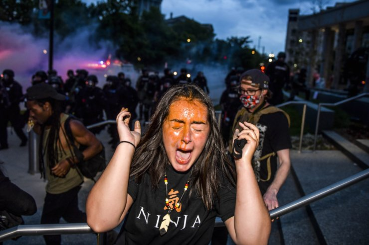A woman reacts after being sprayed by pepper spray next to the Colorado State Capitol as protests against the death of George Floyd continue for a third night on May 30, 2020 in Denver, Colorado. The city of Denver enacted a curfew for Saturday and Sunday nights and Governor Jared Polis activated the Colorado National Guard in hopes of stopping protests that have wreaked havoc across the city. AFP