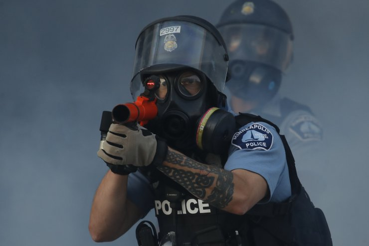 Police fire tear gas and less-lethal rounds at protesters during a demonstration at the intersection of East Lake Street and Hiawatha Avenue, Friday, May 29, 2020, in St. Paul, Minn. Protests continued following the death of George Floyd, who died after being restrained by Minneapolis police officers on Memorial Day. AP