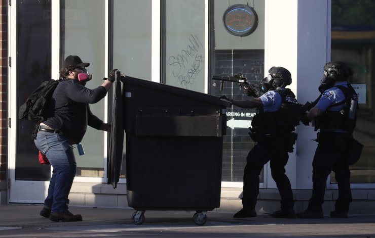 A protester and two Minneapolis police officers on opposite sides of a dumpster during protests over the Minneapolis, Minnesota arrest of George Floyd, who later died in police custody, in St. Paul, Minnesota, USA, 28 May 2020. A bystander's video posted online on 25 May, appeared to show George Floyd, 46, pleading with arresting officers that he couldn't breathe as an officer knelt on his neck. The unarmed black man later died in police custody. EPA