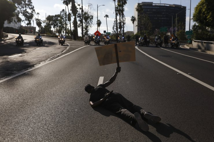 A man lies down on the street in front of police officers while chanting 'I can't breathe' during a protest over the death of George Floyd, Friday, May 29, 2020, in Los Angeles. Floyd died in police custody on Memorial Day in Minneapolis. AP