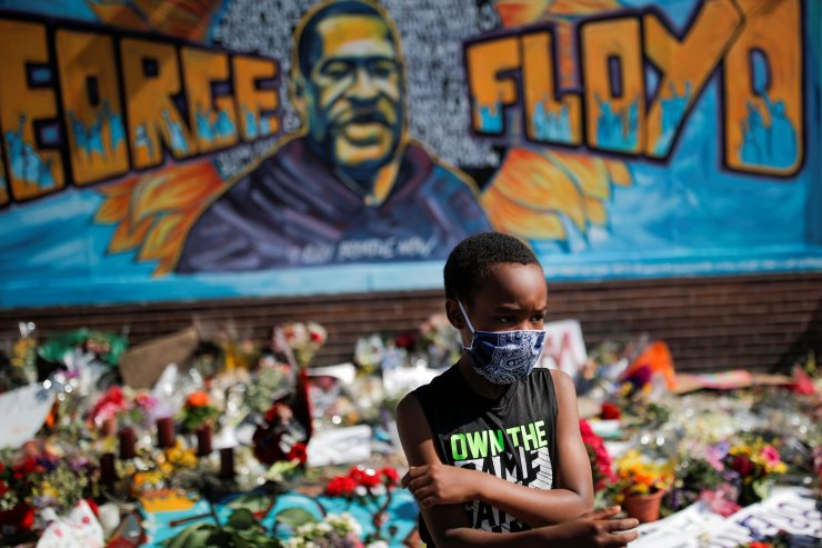 A child wears a protective mask at a makeshift memorial honoring George Floyd, at the spot where he was taken into custody, in Minneapolis, Minnesota, U.S., June 1, 2020. REUTERS