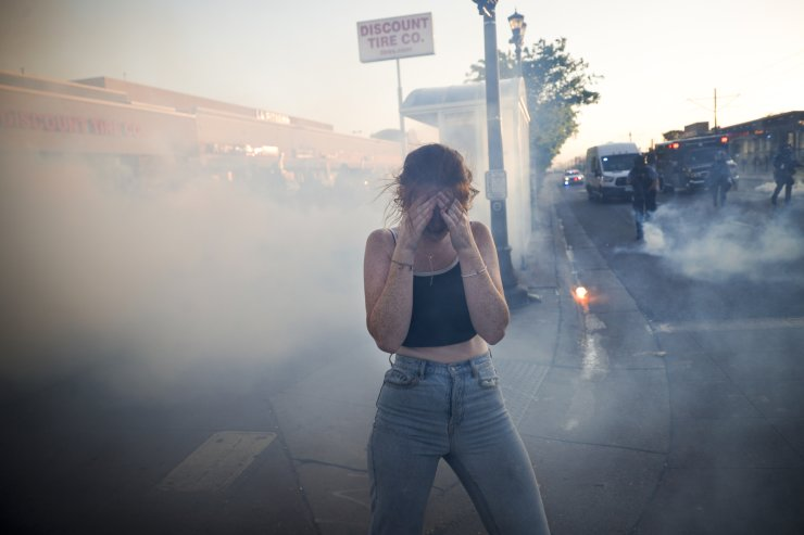 A protestor reacts as she walks through a cloud of tear gas, Thursday, May 28, 2020, in St. Paul, Minn. Protests over the death of George Floyd, a black man who died in police custody Monday, broke out in Minneapolis for a third straight night. AP