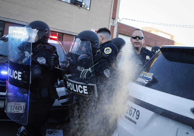 In the May 29, photo, a police officer deploys a can of pepper spray at protesters in Des Moines. Protests have been erupting all over the country after George Floyd died earlier this week in police custody in Minneapolis. AP