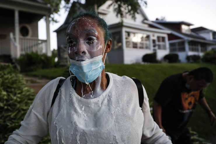 A protestor douses her face with milk after being exposed to tear gas fired by police, Thursday, May 28, 2020, in St. Paul, Minn. Protests over the death of George Floyd, a black man who died in police custody Monday, broke out in Minneapolis for a third straight night. AP
