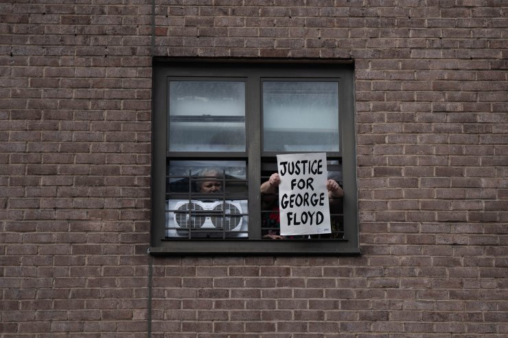 A person holds a sign out of a window on May 30, 2020 in New York City. Minneapolis Police officer Derek Chauvin was filmed kneeling on George Floyd's neck. Floyd was later pronounced dead at a local hospital. Across the country, protests against Floyd's death have set off days and nights of rage as its the most recent in a series of deaths of black Americans by the police. AFP