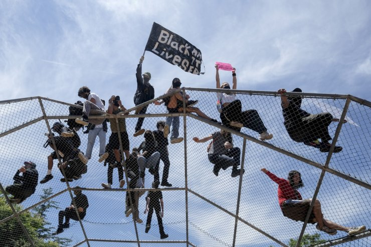 People stand on top of a baseball backstop during a protest over the death of George Floyd in Los Angeles, Saturday, May 30, 2020. Protests across the country have escalated over the death of George Floyd who died after being restrained by Minneapolis police officers on Memorial Day, May 25. AP