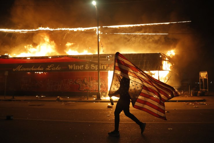 A protester carries the carries a U.S. flag upside, a sign of distress, next to a burning building Thursday, May 28, 2020, in Minneapolis. Protests over the death of George Floyd, a black man who died in police custody Monday, broke out in Minneapolis for a third straight night. AP
