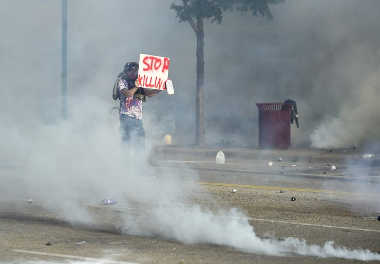A protester stands as teargas is released by police as protesters clash with officers outside a Minneapolis police precinct two days after George Floyd died while in police custody, in Minneapolis, Minnesota USA, 27 May 2020. EPA