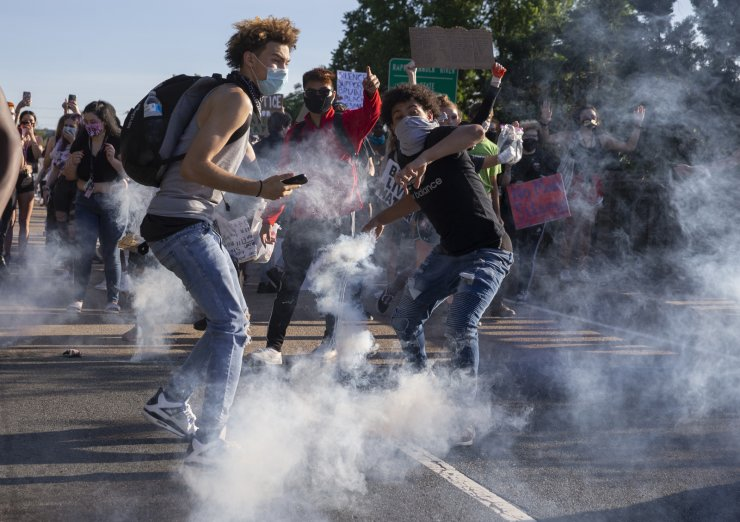 Protesters throw a tear gas canister back toward Stafford County deputies on the Falmouth Bridge in Fredericksburg, Va., Monday, June 1, 2020. Protests continue across the United States over the death of George Floyd, a black man who died after being restrained by Minneapolis police officers on May 25. AP