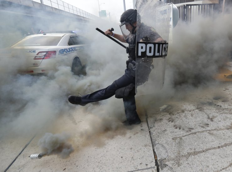 A policeman kicks back a tear gas canister during a demonstration next to the city of Miami Police Department, Saturday, May 30, 2020, downtown in Miami. Protests were held throughout the country over the death of George Floyd, a black man who died after being restrained by Minneapolis police officers on May 25. AP