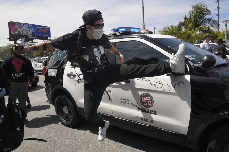 A demonstrator tries to kick the mirror off of a police car during a protest over the death of George Floyd, Saturday, May 30, 2020, in Los Angeles. Protests were held throughout the country over the death of George Floyd, a black man who died after being restrained by Minneapolis police officers on May 25. AP