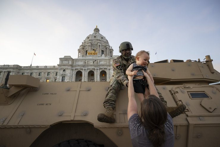 Natasha Robinson passes her son Azrael Hammick, 1, up to Master Sgt. Acie Matthews Jr. during a protest at the at the  State Capitol in St. Paul, Minn., during protests over the death of George Floyd, who died May 25 after being restrained by Minneapolis police. AP