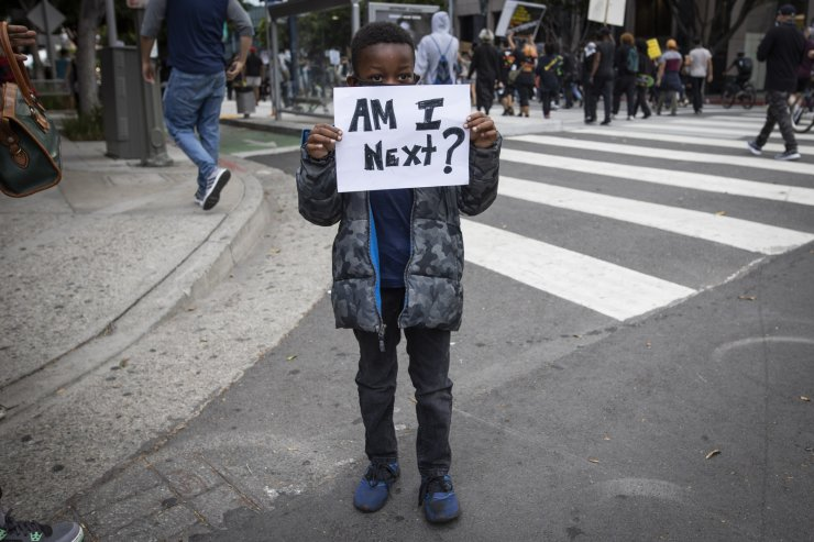 A boy holds a sign during a protest in downtown Los Angeles, Friday, May 29, 2020, over the death of George Floyd, who died in police custody on Memorial Day in Minneapolis. AP