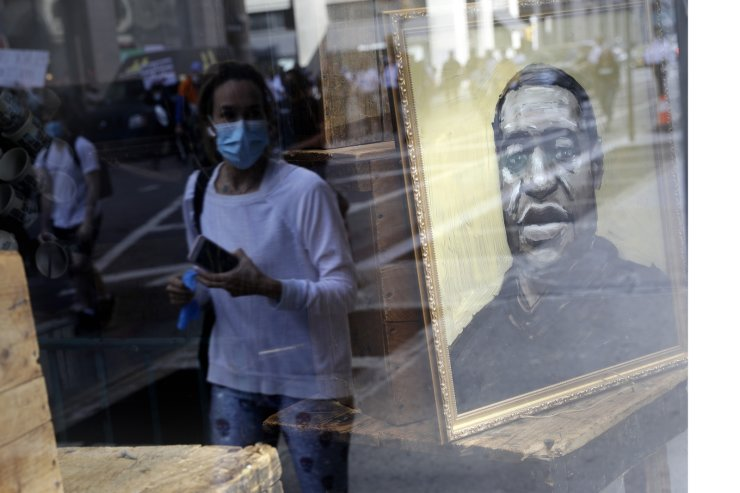 Protesters are reflected in a store window where a portrait of George Floyd is displayed in Manhattan, New York, Monday, June 1, 2020. New York City imposed an 11 p.m. curfew Monday as the nation's biggest city tried to head off another night of destruction erupting amid protests over George Floyd's death. AP