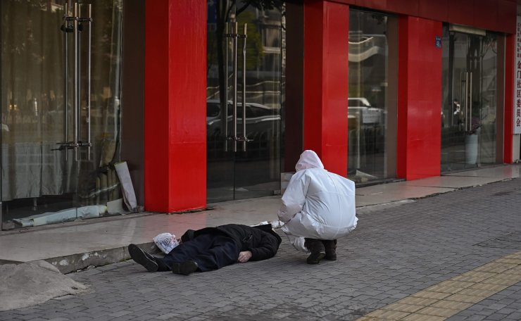 This photo taken on January 30, 2020 shows an official in a protective suit checking on an elderly man wearing a facemask who collapsed and died on a street near a hospital in Wuhan. - AFP journalists saw the body on January 30, not long before an emergency vehicle arrived carrying police and medical staff in full-body protective suits. The World Health Organization declared a global emergency over the new coronavirus, as China reported on January 31 the death toll had climbed to 213 with nearly 10,000 infections. AFP
