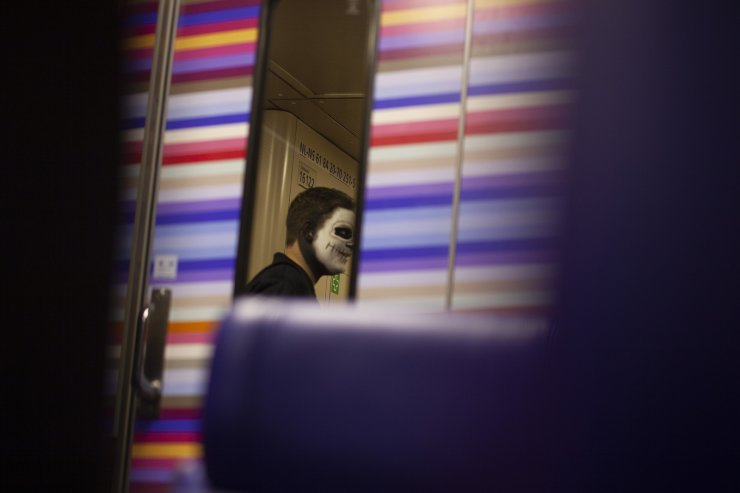 A person wearing skeleton makeup prepares to leave a train as it approaches Amsterdam's Central Station, Netherlands, Sunday, Oct. 27, 2019, on the weekend before Halloween, which is celebrated on Thursday Oct. 31, 2019. AP