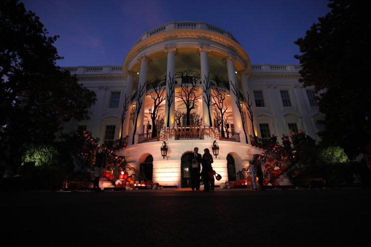 President Donald Trump and first lady Melania Trump give candy to children during a Halloween trick-or-treat event on the South Lawn of the White House which is decorated for Halloween, Monday, Oct. 28, 2019, in Washington. AP