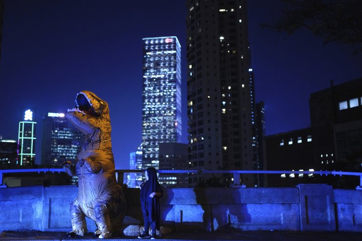 A man dressed as a dinosaur stands in the Mid-Levels area in Hong Kong, Thursday, Oct. 31, 2019. Hong Kong protesters are calling for people to mark Halloween by wearing masks depicting government officials or scary characters. Authorities are bracing for Thursday night's rally, which will put to the test a government ban on face coverings at public gatherings introduced this month to help quell the increasingly violent protests now in their fifth month. AP
