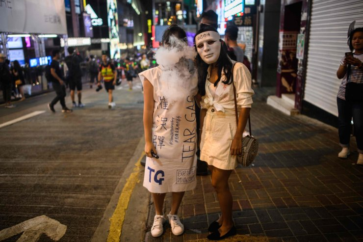 A woman (L) wearing a costume exhales smoke near the Lan Kwai Fong area during Halloween in Hong Kong on October 31, 2019. Hong Kong democracy activists donned Halloween masks lampooning the city's pro-Beijing leaders on October 31, 2019, defying an emergency law that bans face coverings and sparking renewed clashes with police. AP