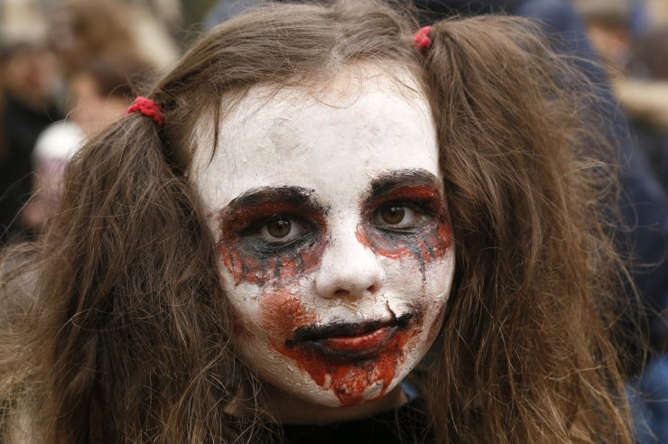 A person dressed as a Zombie poses for a photo as she participates in a 'Zombie Walk' on the weekend before Halloween in central Kyiv, Ukraine Saturday, Oct. 26, 2019. AP