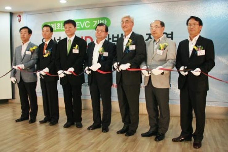 KT Skylife CEO Moon Jae-chul, third from left, cuts the tape with other participants during a ceremony to mark the successful testing of the satellite-based programming for UHD TVs in Seoul, Friday. / Courtesy of KT Skylife