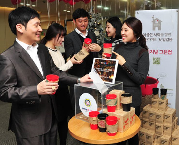 Amway Korea workers check out cups made with environment-friendlymaterials during a launch event for a 'One-for-One Kind Shop' in downtown Seoul, Sunday. Amway donates all the proceeds from these shops to charity. / Courtesy of Amway Korea