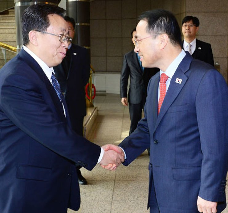 Kim Kyou-hyun, right, vice chief of the presidential National Security Office, and Won Dong-yon, deputy head of the United Front Department of North Korea's ruling Workers' Party, shake hands before holding high-level inter-Korean talks at the border village of Panmunjeom, Wednesday./ Yonhap