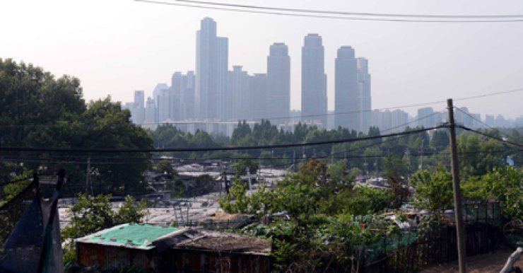 Guryong Village, a shanty town in Seoul's most affluent district, Gangnam, is seen against the backdrop of high-rise buildings. / Korea Times file