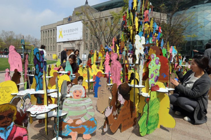 Members of the Korea Green Foundation make artwork in memory of the victims of the Sewol ferry sinking, and to wish for a safer society, at Seoul Square, Wednesday. / Yonhap
