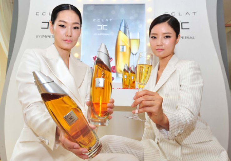 Models display Pernod Ricard's new low-alcohol spirit Eclat by Imperial, which has pomegranate flavor to cater to female drinkers' delicate taste, during a launch event in southern Seoul, Wednesday. The mild drink, with 31 percent alcohol content, is priced at 36,300 won. / Yonhap