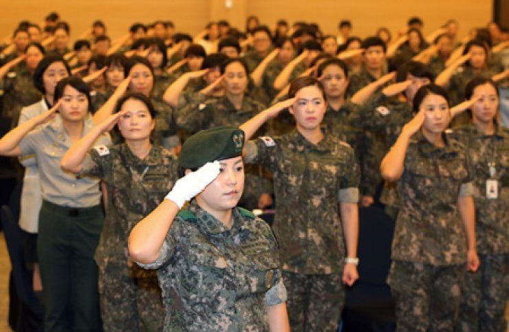 Female soldiers salute to the national flag during a ceremony to mark the 65th anniversary of women's entry into the armed forces, at the MND Convention in Yongsan-gu, Seoul, Friday. / Yonhap