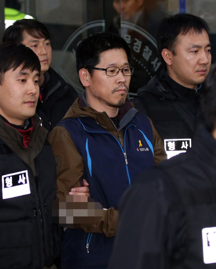 <span>Han Sang-gyun, center, head of the Korean Confederation of Trade Unions (KCTU), walks toward a patrol car to be transferred to the prosecution from Namdaemun Police Station, Seoul, Friday. The Seoul Metropolitan Police Agency sent the opinion to prosecutors that he should be indicted for sedition for allegedly organizing an illegal rally on Nov. 14. / Yonhap</span><br /><br />