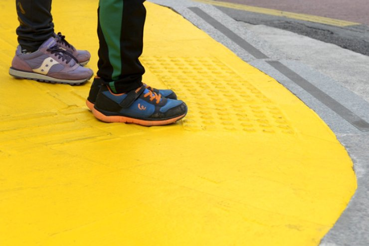 Children stand on a 'yellow carpet' waiting for a crossing sign at a crosswalk. Experts believe this will help children avoid car accidents at or near crosswalks in school zones. / Courtesy of the International Child Rights Center