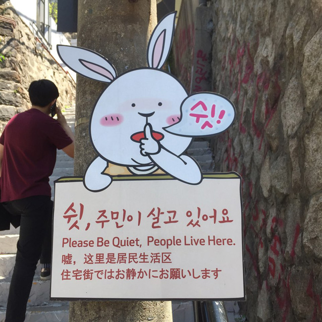 Visitors take photos in front of a mural at Ihwa Mural Village in central Seoul. As hundreds of domestic and foreign tourists come to see the murals, residents complain of the noise they make and the wastes they leave behind.