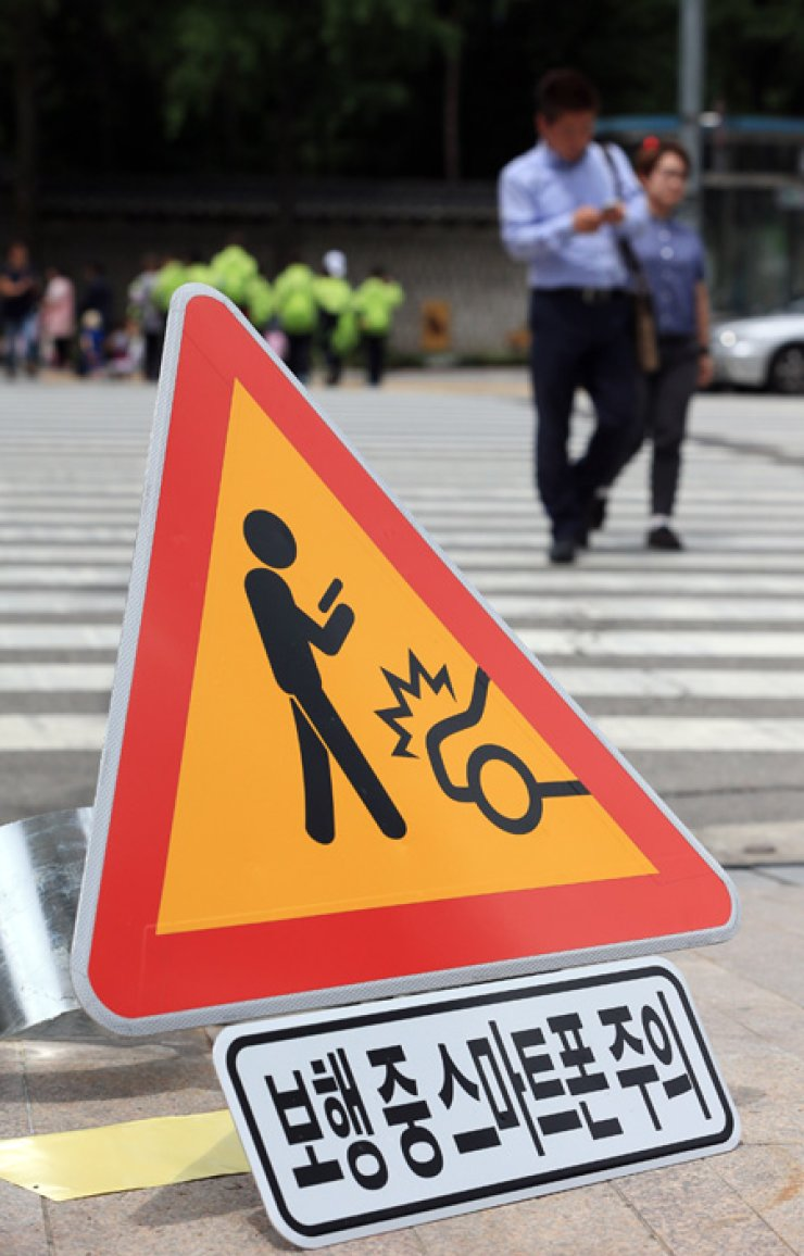 A sign warning people not to use smartphones while crossing the road waits to be installed in front of City Hall in downtown Seoul, Thursday. / Yonhap