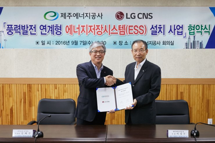LG CNS Vice President Kim Tae-geuk, left, poses with Jeju Energy Corporation CEO Lee Sung-goo, after signing a contract for a joint energy storage system (ESS) project, at the latter's headquarters on the nation's southern island of Jeju, Wednesday. The partnership will allow the IT service affiliate of LG Group to integrate its ESS with major wind power plants there. / Courtesy of LG CNS