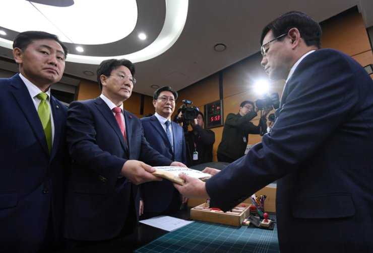 Rep. Kweon Seong-dong of the Saenuri Party, chief of the National Assembly Legislation and Judiciary Committee, second from left, hands in the impeachment resolution to the Constitutional Court in central Seoul, Friday evening./ Yonhap