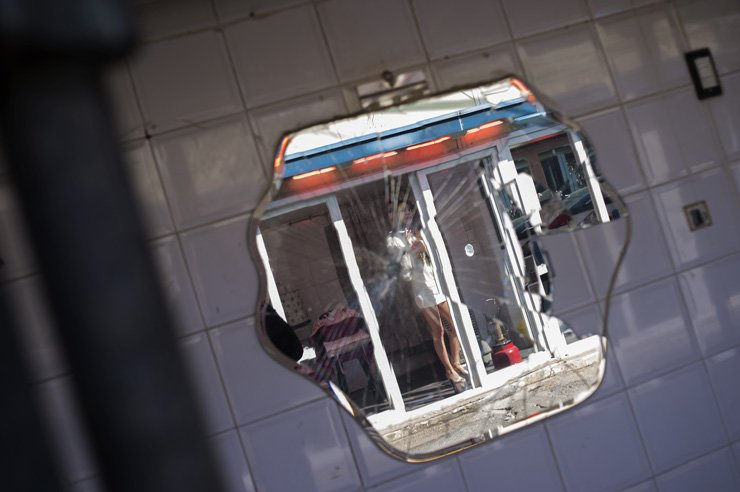 A broken mirror reflects a prostitute across the street at Cheongnyangni 588. An urban redevelopment project will soon wipe out the red-light district despite protests from the remaining sex workers and other tenants. High-rise residential and commercial buildings will replace the red-light district which opened nearly 80 years ago. / Korea Times photos by Shim Hyun-chul