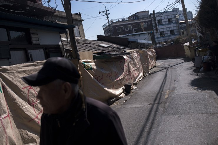 A man walks past brothels that are now covered up by tarpaulin at Cheongnyangni 588, Jeonnong-dong, Seoul. A redevelopment project will wipe out the red-light district, after developers forcibly evict the remaining sex workers and tenants.