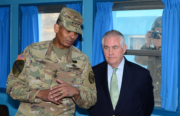 U.S. Forces Korea Commander Gen. Vincent Brooks, left, speaks to U.S. Secretary of State Rex Tillerson, who is on a two-day visit to South Korea, at the truce village of Panmunjeom on the inter-Korean border,Friday, while a North Korean soldier takes a photo of them from outside. / Joint press corps