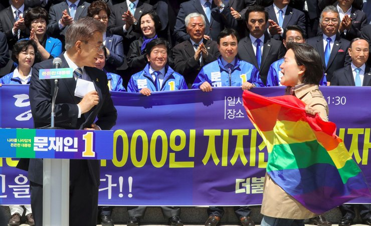 A rights activist for sexual minorities holding a rainbow flag approaches presidential frontrunner Moon Jae-in at the National Assembly in Seoul, April 26, to protest Moon's anti-gay comment during his election campaign event . /AP-Yonhap