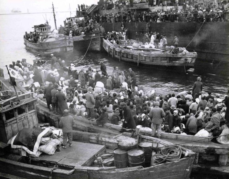 The file photo taken on Dec. 19, 1950, shows refugees aboard fishing boats and a military ship being evacuated from Hungnam, North Korea. The parents of Moon Jae-in, the winner of the presidential election, were among some 100,000 refugees from the North who eventually settled in Busan and nearby Geoje Island. / Korea Times