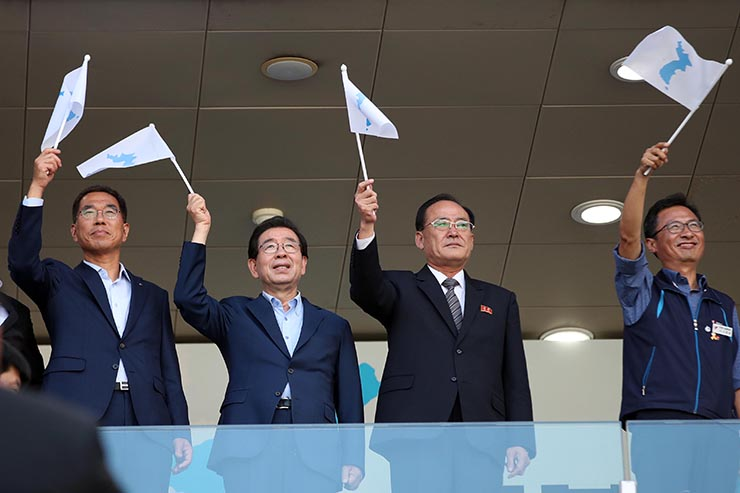 South Korean supporters wave the unification flags during a friendly football match at the Sangam World Cup stadium in Seoul, on Saturday. EPA