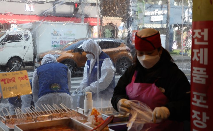 Workers wearing protective gears spray disinfectant as a precaution against the coronavirus at a market in Seoul, South Korea, Monday, Feb. 24, 2020. Korea Times photo by Choi Won-suk