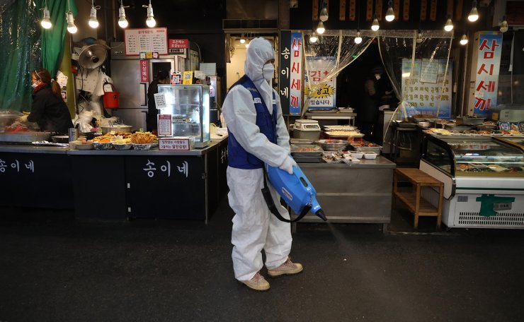 A worker wearing protective gear sprays disinfectant as a precaution against the coronavirus at a market in Seoul, South Korea, Monday, Feb. 24, 2020. Korea Times photo by Choi Won-suk